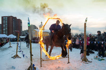 show ring: St.Petersburg, Russia - January 7, 2016: The show riders on a city celebration of Christmas. Jumping through the ring of fire.