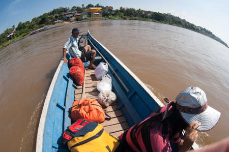 boater: Chiang Khong, Thailand - 1 February 2014: The boat crosses the border between the Thai city of Chiang Khong and Huai Hai Lao. In the boat, tourists and locals