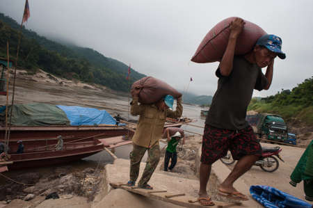 docker: Pak Beng, Laos - February 3, 2014: Working stevedores unload bags of food out of the boat and dipped them into trucks at the pier of the Mekong River in the daytime Editorial