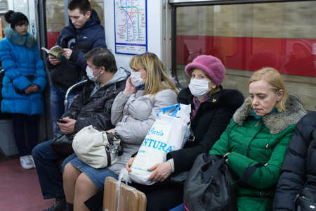 swine flue: St.Petersburg, Russia - January 29, 2016: People are protected against swine flu by a gauze mask  when moving around the city by public transport and the metro. Flu epidemic.