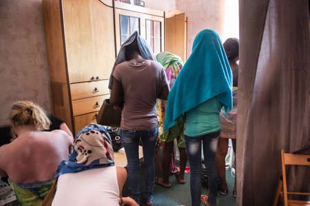 exploitation: St. Petersburg, Russia - July 4, 2013: The women hide their faces with towels draped over his head during a police raid on brothels of the city to identify those involved in prostitution.