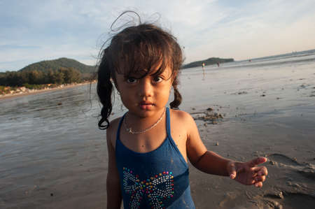 molluscs: Lanta Krabi, Thailand - February 2, 2014: A girl plays on the beach while their parents collect marine molluscs at low tide