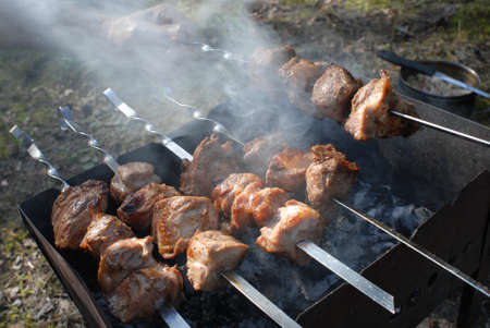chafing dish: Cooking pork on skewers on the grill in the smoke. Summer day