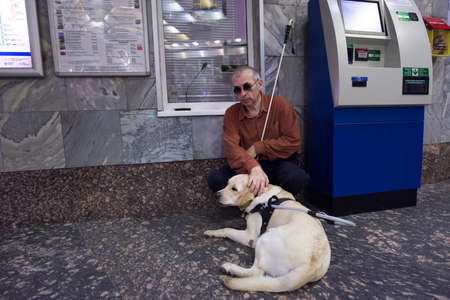 helpmate: St. Petersburg, Russia - July 17 2015: School to teach the blind to use the subway with dogs allowed. Blind man with a dog at the box office Metro. Editorial