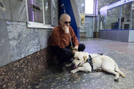 San Petersburgo, Rusia - 17 de julio de 2015: escuela para enseñar a los ciegos a usar el metro con perros permitidos. ciego con un perro en la taquilla de metro.