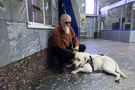 St. Petersburg, Russia - July 17 2015: School to teach the blind to use the subway with dogs allowed. Blind man with a dog at the box office Metro. Editoriali