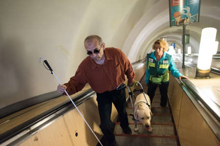 helpmate: St. Petersburg, Russia - July 17 2015: School to teach the blind to use the subway with dogs allowed. Blind man with guide dog on the escalator with instructor Editorial