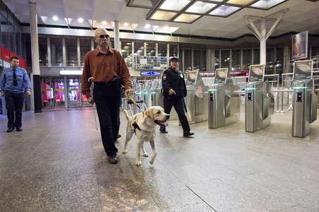 San Petersburgo, Rusia - 17 de julio de 2015: escuela para enseñar a los ciegos a usar el metro con perros permitidos. El ciego se dirige a los torniquetes del metro
