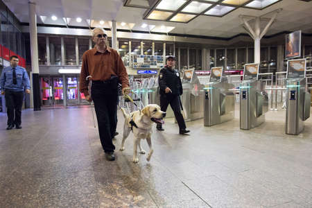 blind people: St. Petersburg, Russia - July 17 2015: School to teach the blind to use the subway with dogs allowed. The blind man goes to the subway turnstiles