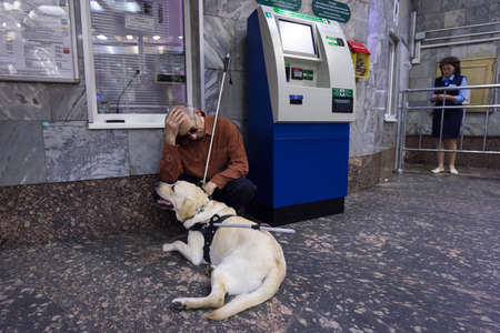 sightless: St. Petersburg, Russia - July 17 2015: School to teach the blind to use the subway with dogs allowed. Blind man with a dog at the box office Metro. Editorial
