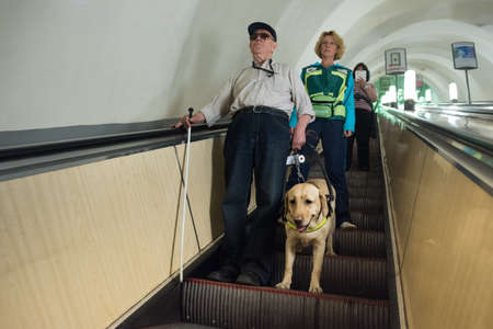 blind person: St. Petersburg, Russia - July 17 2015: School to teach the blind to use the subway with dogs allowed. Blind man with guide dog on the escalator with instructor Editorial