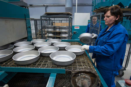 teflon: St.Petersburg, Russia - January 29, 2016: Production Line for manufacturing  pans with Teflon coating. Woman-operator controls the process Editorial
