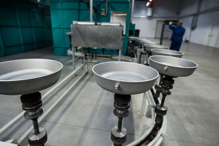 St.Petersburg, Russia - January 29, 2016: Production Line for manufacturing  pans with Teflon coating. Woman-operator controls the process Редакционное