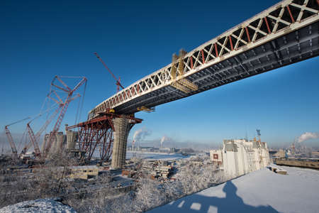 gat: Saint-Petersburg, Russia - January 23, 2016: Construction of the city expressway highway. The high bridge over the sea in the harbor of the island Kanonersky area. The bridge directly above the residential area. Winter, a bright sunny day.
