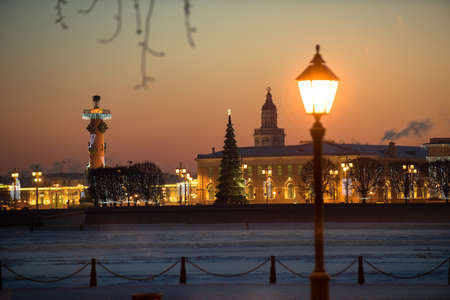 View of the evening city decorated with lights. In the foreground a street light. In the background, the main attractions - rosstralnye columns. Russia, Saint-Petersburg.