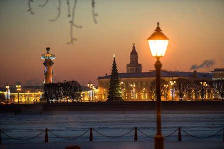 Vue de la ville du soir décorée de lumières. Au premier plan un réverbère. En arrière-plan, les principales attractions - colonnes rosstralnye. Russie, Saint-Pétersbourg. Banque d'images