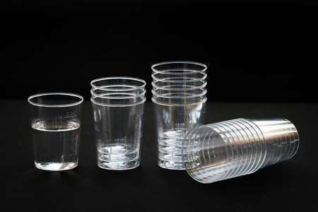 The disposable clear plastic cups to 40 ml with graduation to receive small portions of beverages, water and other liquids. Close-up on a black background with blur cups in the background, jet of water being poured into a glass, pure water in the cup