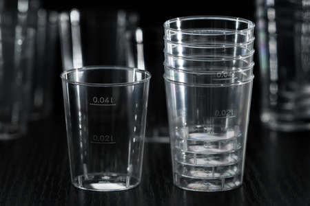 The disposable clear plastic cups to 40 ml with graduation to receive small portions of beverages, water and other liquids. Close-up on a black background with blur cups in the background