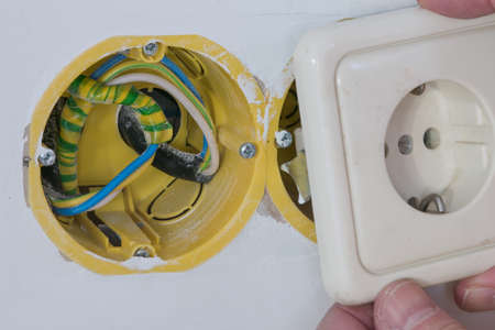 unprotected: Household electrical box for connecting an electrical outlet in a residential building in a white unpainted wall of yellow color with wires during the working process podklyucheniyayu.