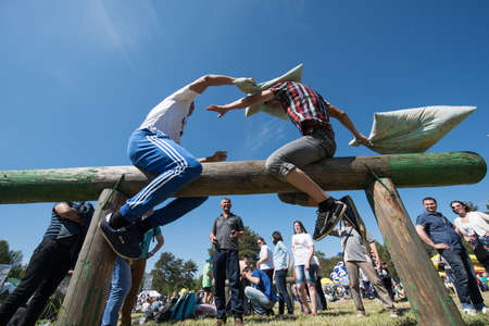 field work: St. Petersburg, Russia - June 13 2015: Two young guys trying to knock each others pillows, a fun game at the traditional celebration to mark the end of the Tatars of spring field work Sabantuy