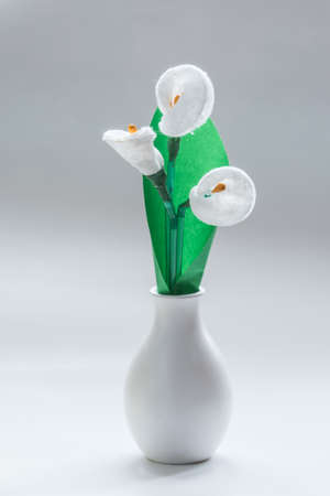 callas: Flowers callas handmade made from scrap materials - cotton swabs, tubes for juice, clay, wool, plastic bottles, clay. In a white vase.