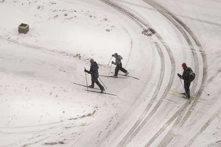 snowfalls: Saint-Petersburg, Russia - February 27, 2016: Three skiers cross the muddy footprints of cars. Top view, winter, snow.