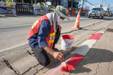 armbands: Chiang Khong, Thailand - December 3, 2014: Road workers paint borders the towns main road. On a hot day, the men protected their faces from the sun hats and armbands. Editorial