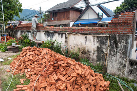 leveler: Pai, Thailand - November 26, 2014: A young man with a hat on a clear sunny day is building a wall from a red brick building. Thai street of a small town in the north of the country.