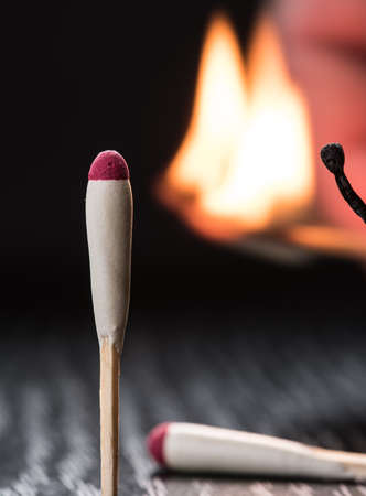 eagerness: Tourist matches for use in difficult weather conditions - strong wind and rain. Burning match on a dark background.