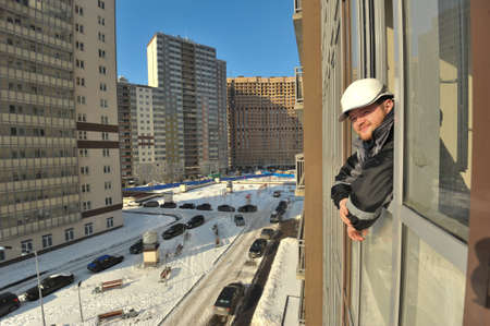 executive apartment: Saint-Petersburg, Russia - March 1, 2016: A new residential complex of high-rise buildings at the stage of completion. Builder in a helmet looks out of the window of the new apartment.