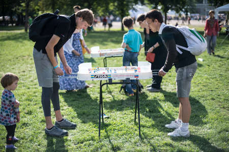 Saint-Petersburg, Russia - August 16, 2015: Festival of board games in the central city park. Young men playing table hockey on a green lawn Editorial