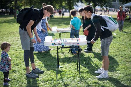 hockey cesped: San Petersburgo, Rusia - 16 de agosto de 2015: Festival de juegos de mesa en el parque central de la ciudad. los hombres jóvenes jugando al hockey de mesa en un césped verde