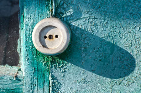bad condition: White socket on the outside of the wooden wall of a house painted in green and turquoise colors. The paint is cracked and peeling. The texture of a bad condition and quality.