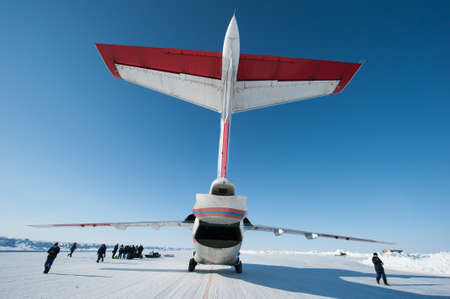 Drifting ice floe is in the neutral waters of the Arctic Ocean - April 28, 2011: The Russian aircraft AN-74P MOE on an ice runway near the polar station SP-38  drifting on an ice floe in the area of North Pole Editorial