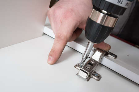 screwing: screwing the furniture hinge leaf to the white cabinet in the small wholesale furniture company Stock Photo