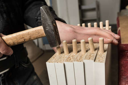 furniture part: Carpenter wooden sticks pins into the wood particle board that is part of a furniture cabinet.