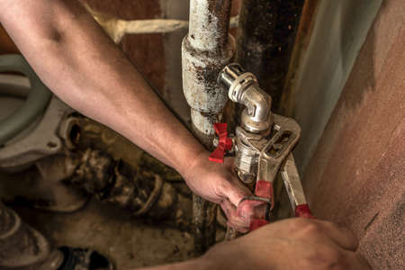 working hands: Plumber man replaces the tap in the bathroom. Fasten faucet using a wrench to rusty water pipe
