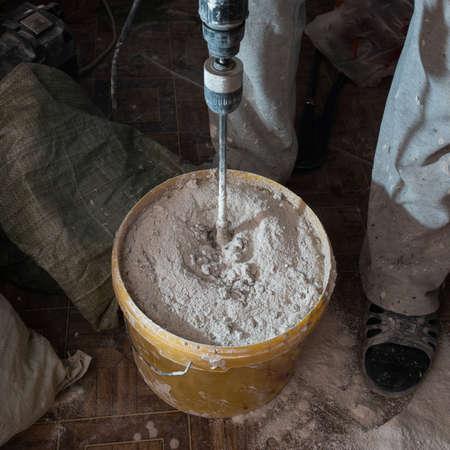 Bouwvakker man roert het mengsel in de emmer constructie voor uitlijning en stopverf muren van het appartement met de hulp van een krachtige boor.