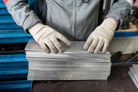 metalline: small stack of steel plates on the bench miller, hand in working gloves