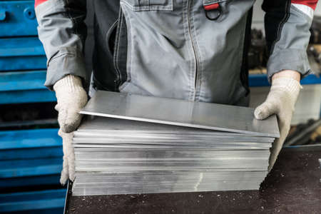milling rolling: small stack of steel plates on the bench miller, hand in working gloves