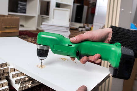 furniture part: Carpenter drills a hole in the component parts of a white kitchen cabinet for fastening pins wall cabinets. Small wholesale furniture factory, part of the technological assembly line. Stock Photo
