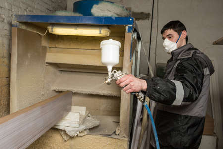 intake: Saint-Petersburg, Russia - March 17, 2016: Carpenter painter paints the furniture board with a spray gun on the production line small wholesale furniture factory on the background of the air intake. Protective face mask.