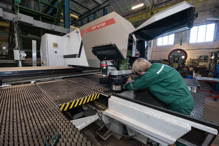 milling machine: Saint-Petersburg, Russia - March 23, 2016: Worker young man miller  is working by milling machine in working overalls, shop engineering plant. The large milling machine.