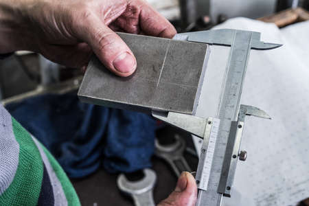 thickness: Control the size of the metal parts with a caliper measuring device. Shop metalworking plant.