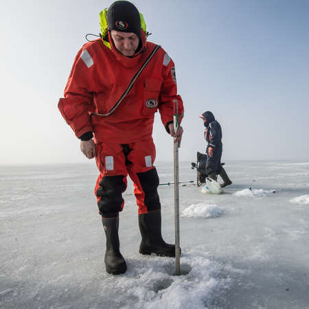 Saint-Petersburg, Russia - March 27, 2016: A member of the rescue team checks the thickness of the ice in the Gulf of Finland, where the ice fishermen out.
