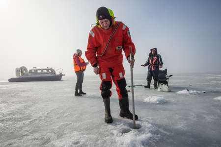 hovercraft: Saint-Petersburg, Russia - March 27, 2016: A member of the rescue team checks the thickness of the ice in the Gulf of Finland, where the ice fishermen out.