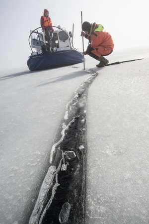 thickness: Saint-Petersburg, Russia - March 27, 2016: A member of the rescue team checks the thickness of the ice in the Gulf of Finland, where the ice fishermen out.