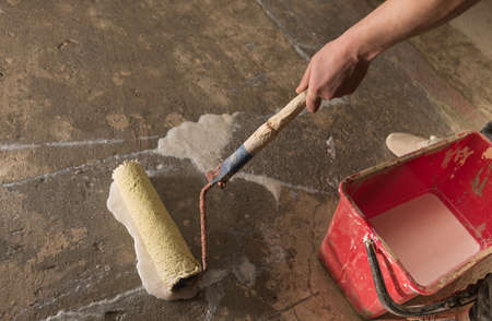 priming: Priming Concrete floor before laying tiles on it, the final preparatory stage for strengthening the surface