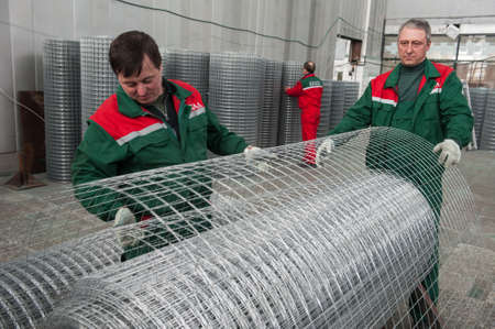 netting: Leningrad, Russia - April 6, 2012: Plant for production of fences. Workshop packing wire mesh netting. Mesh netting in rolls