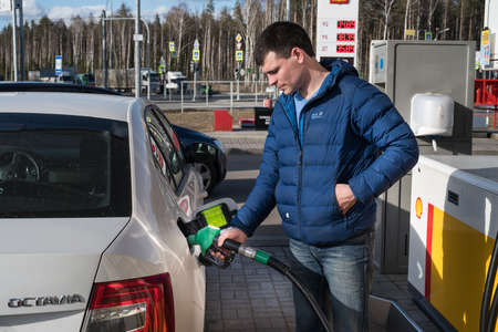 opec: Saint-Petersburg, Russia - April 7, 2016: A man 30-35 years fills his car with petrol at a petrol station Shell Editorial